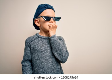 Young little caucasian kid wearing internet meme thug life glasses over isolated background looking stressed and nervous with hands on mouth biting nails. Anxiety problem.