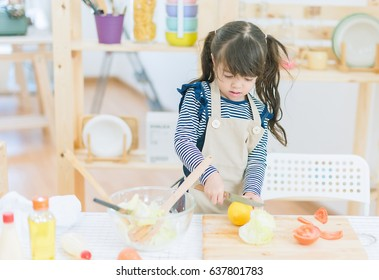 Young little girl chef preparing vegetable soup in kitchen,family and relaxing concept.