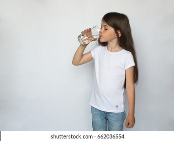 Young little girl drinking water, isolated on a white background