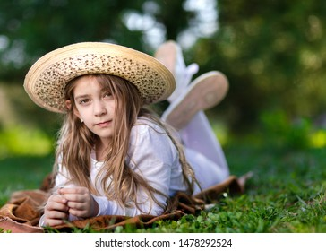 Young little girl with hat lying on grass in park.