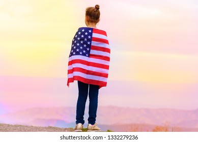 Young little girl holding flag of America USA at sunset outdoors. Gradient toned image.
