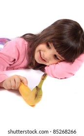 Young little girl laying on white background holding a banana and smiling