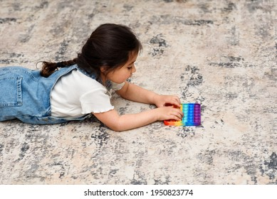 Young Little Girl Lies On The Floor At Home Playing Poppit-New Fidget Toy, Popular With Kids, Helps Them To Concentrate. Child Lies On The Floor Playing With The Pop It Fidget Toy.