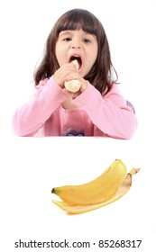 Young little girl making a funny face eating a healthy banana