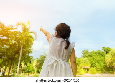Young little girl pointing with his finger to the sunlight on blue sky