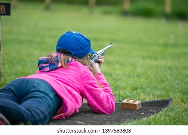 Young little girl shooting bolt action 22 rifle prone laying on the ground.