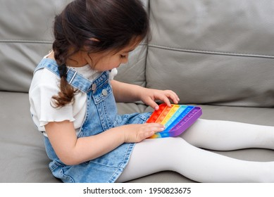 Young Little Girl Sitting On The Sofa At Home Playing Poppit-New Fidget Toy, Popular With Kids, Helps Them To Concentrate. Child Playing With The Pop It Fidget Toy.