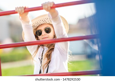 Young little girl with sunglasses and hat at playground.
