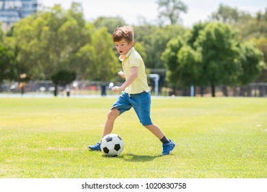 young little kid 7 or 8 years old enjoying happy playing football soccer at grass city park field running and kicking the ball excited in childhood sport passion and healthy lifestyle concept