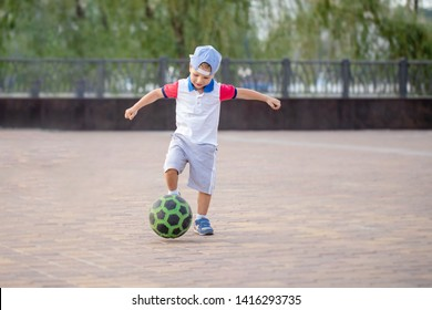 young little kid  enjoying happy playing football soccer in city park hits the ball gives a pass and likes to play in the street oblivious to people