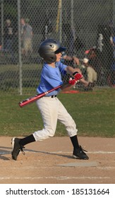 A Young Little League Batter Swings at a Pitch