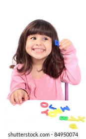 Young little preschool girl with funny expression playing with letters and holding up the number four showing her age