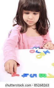 Young little preschool girl with funny expression playing with letters and numbers