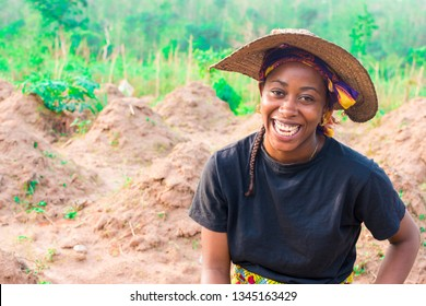 young local african female farmer laughing in her farm