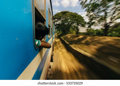 Young local boy looking through the window of a blue train