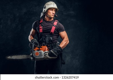 Young logger wearing protective clothing and helmet posing with a chainsaw in a dark studio and looking sideways