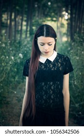 Young lolita girl in the forest in fairytale mood - Wednesday Addams style - Portrait of a young woman in a gloomy, enigmatic mood