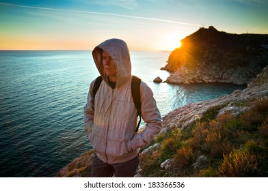 Young lone traveler on a hill at sunset