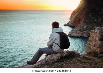 Young lone traveler sits on a hill and enjoys sea views