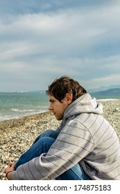 Young lonely man dressed blue jeans and grey jacket sitting on the beach and looking at the sea. Loneliness, sadness, depression. Sad alone. The treatment of depression. On the sea shore.