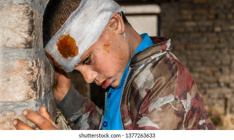 a young lonely missing crying injured child is frightened cause of war and child abuse and having bandage on his head