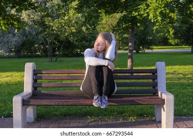 Young lonely sad girl sits on a bench