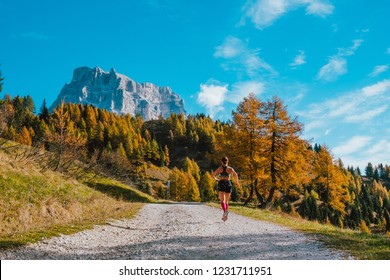 young lonely woman skyrunner running toward rocky mountain in italian alps in sunny day seen from behind