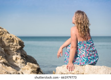 Young long blond hair woman sitting on a rocks at sea