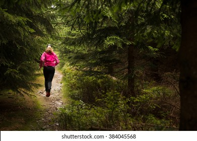 young long hair woman running on the muddy trail in the dark forest after the rain