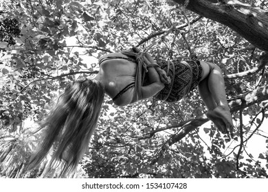 A young long haired girl is hanging from a tree tied up with ropes in shibari fetish practice - Black and white extreme low angle - Barefoot girl with her hands tied in her back - Sensual fetish