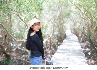 young long haired girl in straw hat holding camera on the wooden bridge