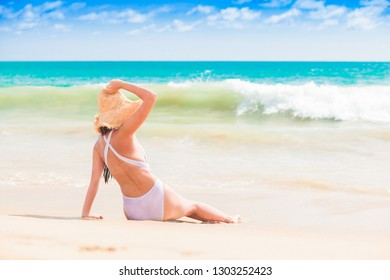 young long haired girl in white bikini tanning at tropical beach