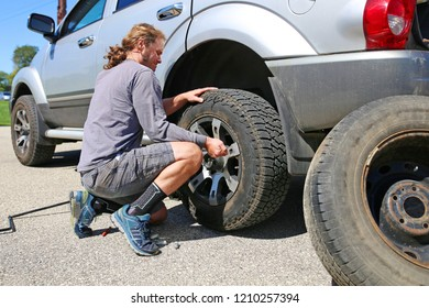 A young, long haired man is using force to change is blown flat tire on his Silver SUV, with his spare sitting by on the side of the road.