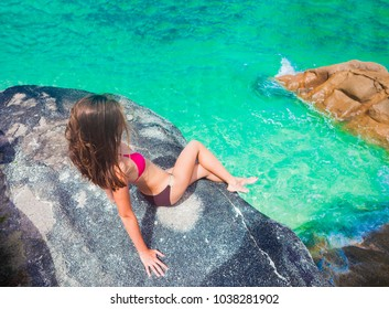 young long haired woman in onepiece swimsuit relaxing on the rocks over the sea. Mahe Island, Seychelles