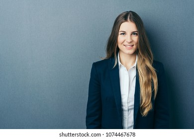 Young long-haired cheerful woman wearing elegant jacket standing against blue wall with copy space
