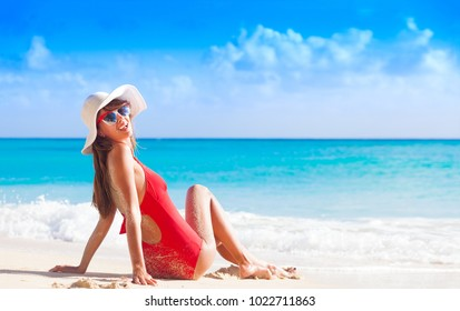 young longhaired girl in red swimsuit tanning at tropical beach