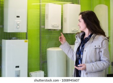 Young longhaired woman choosing heating water converter in hypermarket