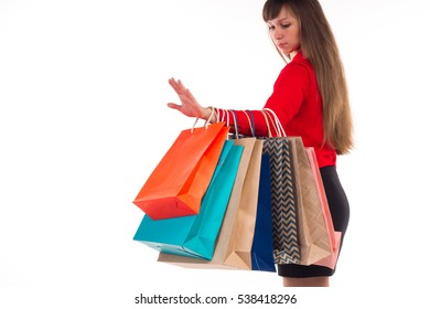 Young long-haired woman holds her purchases, many colorful paper bags, packages in her hands after shopping