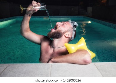 Young loose playboy in a swimming pool, pouring champagne into his mouth from a glass, wine splashing all over his face, wearing diving goggles and inflatable arm band yellow star