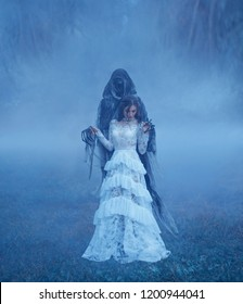 Young Lord's Bride in white vintage mesh translucent dress and silver necklace is standing on the frozen autumn grass in a thick blue fog in monster hands. Beauty and the Beast in haze and winter mist