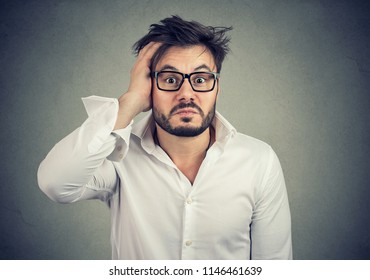Young lost and dumbfounded man with hand on head wearing glasses and looking perplexed at camera on gray background
