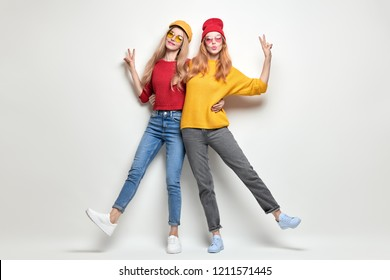 Young lovable Hipster Girl in Yellow Red jumper, Fashion Trendy denim. Two Playful Friends Having Fun, Kiss Face Expression in Stylish Autumn Outfit. Happy Woman Smiling, positive emotion