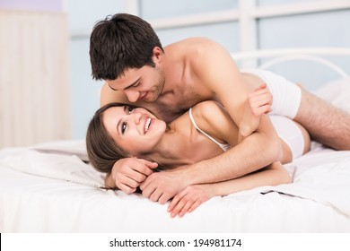 Young love couple in bed, romantic scene in bedroom