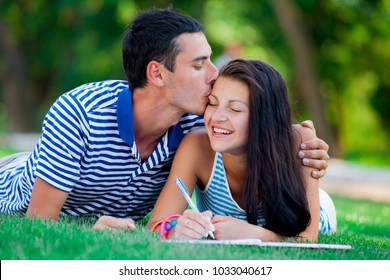 Young in love couple with in blue clothing in green summertime park
