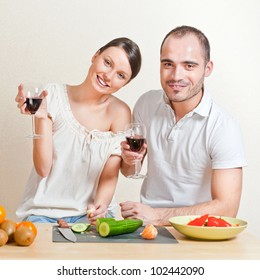 Young love couple cooking and drinking red whine from beautiful glasses. Big copyspace