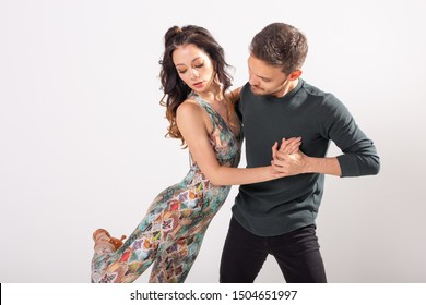 Young love couple dancing social danse kizomba or bachata over white background with copy space