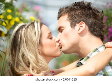 Young love couple smiling among lots of flowers