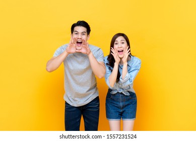 Young lovely asian couple yelling with hands cup around mouths isolated on yellow studio background