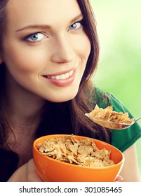 young lovely brunette woman eating muesli or cornflakes, outdoor