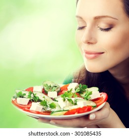 Young lovely brunette woman with plate of salad, outdoor